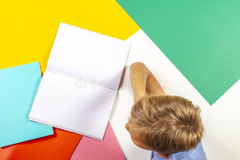 Het notitieboekje die van het de lezingsboek van de leerlingsjongen thuiswerk doen Hoogste mening, kleurrijke achtergrond stock afbeelding