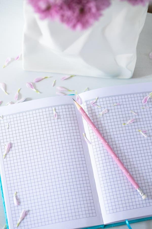 Het notitieboekje met Potlood en Kleine Roze Bloemblaadjes bloeit dichtbij Witte Va stock afbeelding