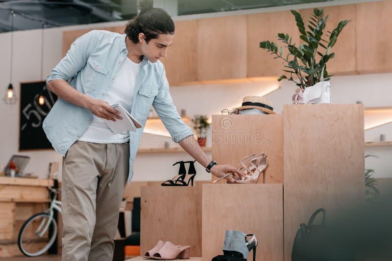 Het notitieboekje van de jonge mensenholding met potlood terwijl het bekijken schoenen en het werken in boutique stock afbeelding