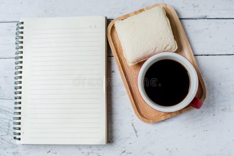 Het notitieboekje van de tonijnsandwich en koffie rode kop royalty-vrije stock afbeeldingen