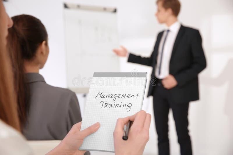 Het notitieboekje van de vrouwenholding met tekst MANAGEMENT TRAINING bij presentatie stock fotografie