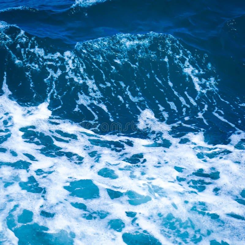Het oceaanoverzees van het golfwater van gegolft water met witte golf borrelt dichtbij de grote boot op de zomer stock afbeeldingen