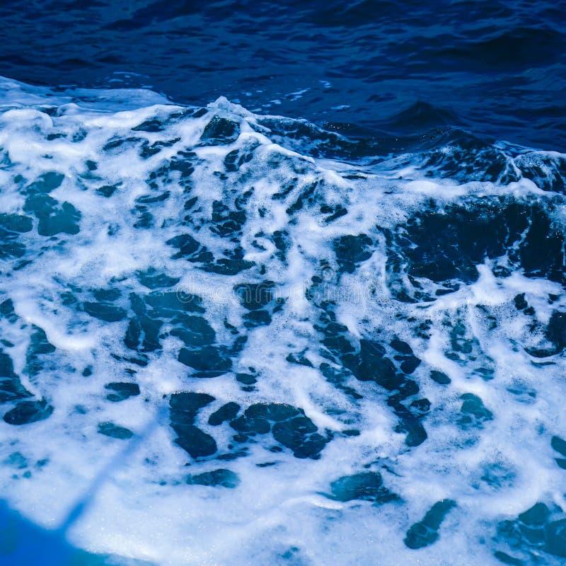 Het oceaanoverzees van het golfwater van gegolft water met witte golf borrelt dichtbij de grote boot op de zomer royalty-vrije stock foto