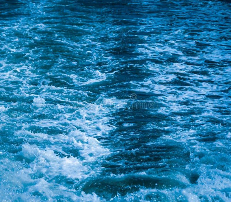 Het oceaanoverzees van het golfwater van gegolft water met witte golf borrelt dichtbij de grote boot op de zomer stock fotografie