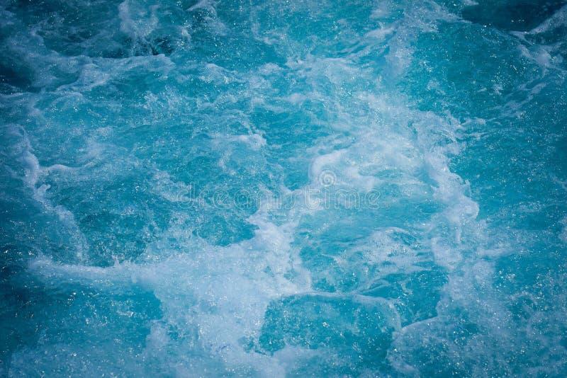 Het oceaanoverzees van het golfwater van gegolft water met witte golf borrelt dichtbij de grote boot op de zomer stock afbeelding
