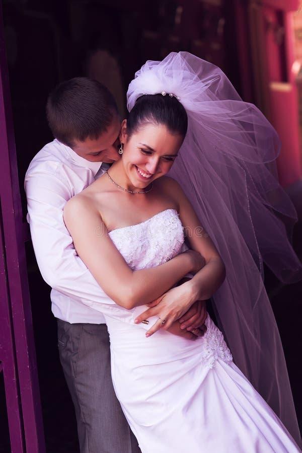 Het omhelzen van bruid en bruidegom het lachen royalty-vrije stock foto