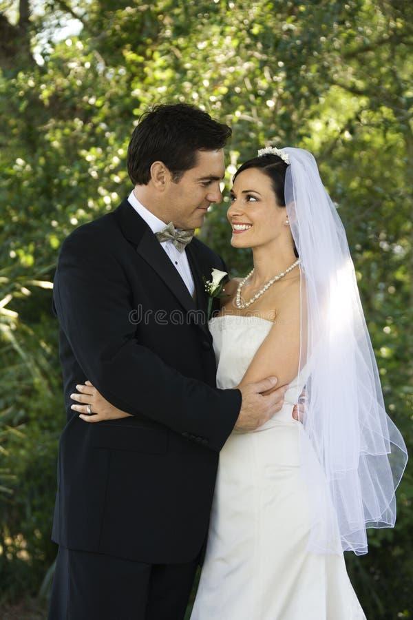 Het omhelzen van de bruid en van de bruidegom. stock afbeelding
