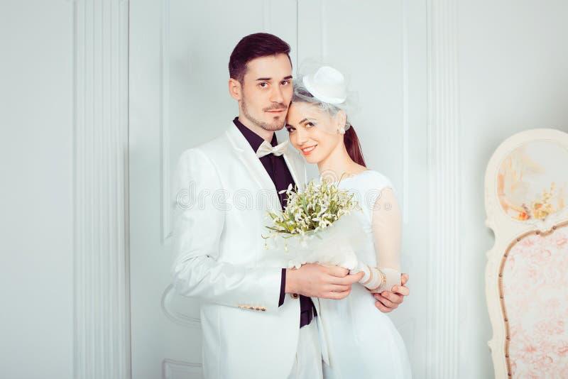 Het omhelzen van mooie jonggehuwden in elegant binnenland stock fotografie