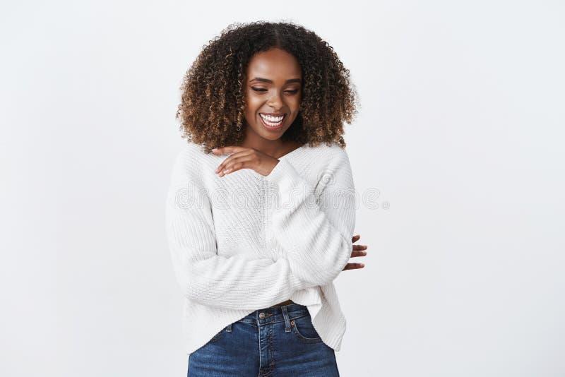 Het onbezorgde geamuseerde positieve Afrikaanse Amerikaanse krullend-haired vrouwen witte sweater luid lachen uit ziet vreugdevol royalty-vrije stock foto