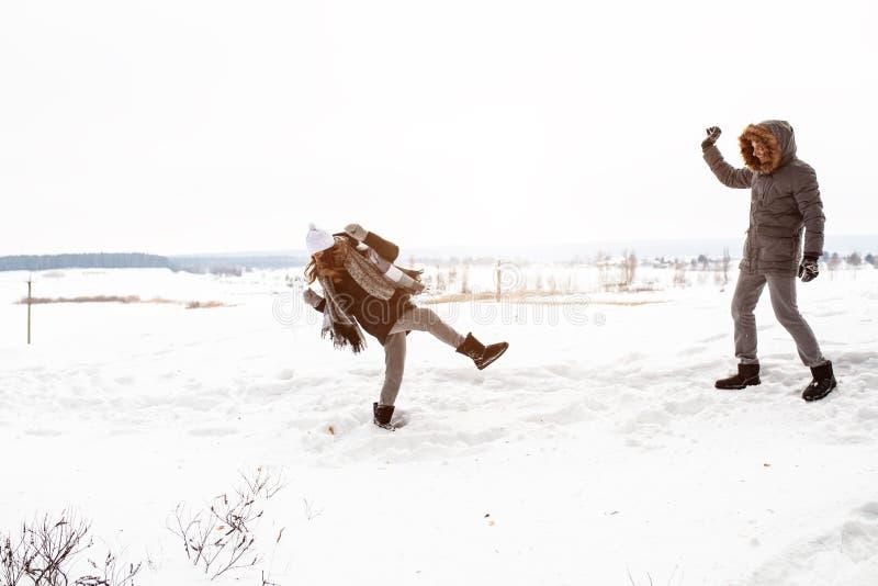 Het onbezorgde gelukkige jonge paar die pret samen in sneeuw in de winter het bos werpen hebben doet escaleren bij elkaar tijdens royalty-vrije stock afbeelding