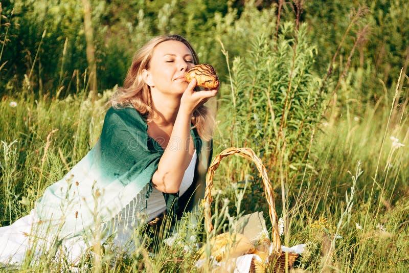 Het onbezorgde meisje die op het gazon in het de zomerpark rusten en heeft een croissant stock foto's