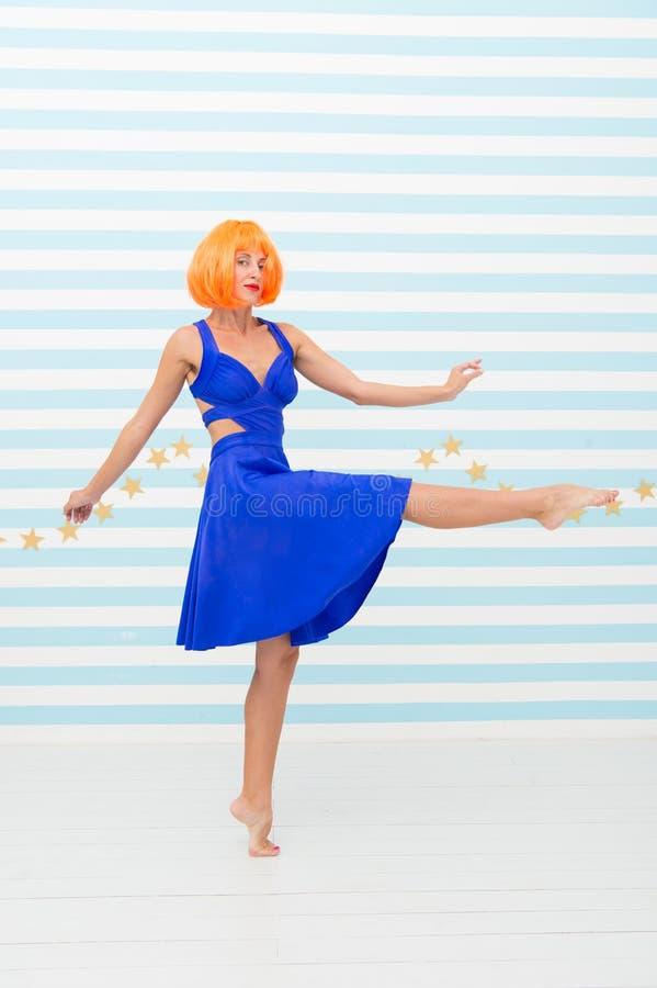 Het onbezorgde meisje met gekke blik maakt stap Zo veel pret gek meisje met oranje haar die blootvoets dansen Totaal onbezorgd stock foto's