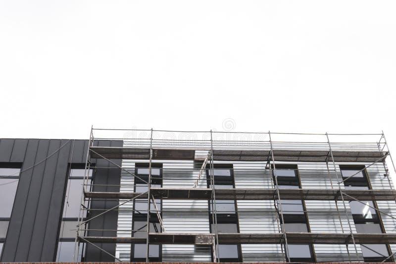 Het onder ogen zien van de werken, installatie van materiaal, steiger Bouw en van de bouwdiensten concept, achtergrond met plaats stock afbeeldingen