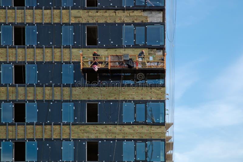 Het onder ogen zien van het gebouw met een geventileerde voorgevel en hijstoestel met arbeiders royalty-vrije stock afbeelding
