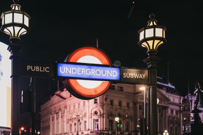 Het Ondergrondse teken van Londen bij de ingang van Piccadilly Circus-post, Londen, het UK, bij nacht royalty-vrije stock fotografie
