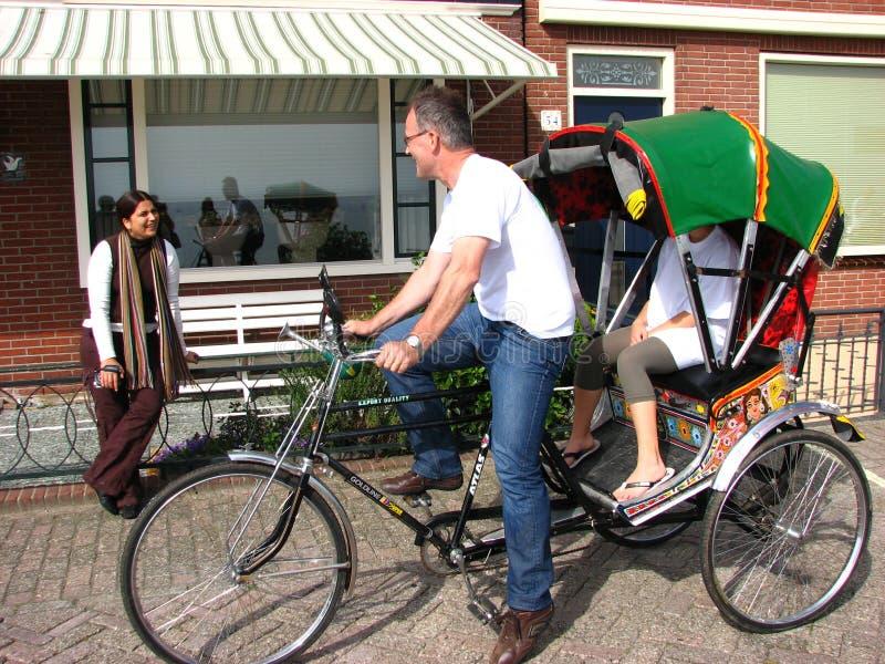 Het onderhandelen van de toerist prijs op fietstaxi, Volendam stock afbeelding