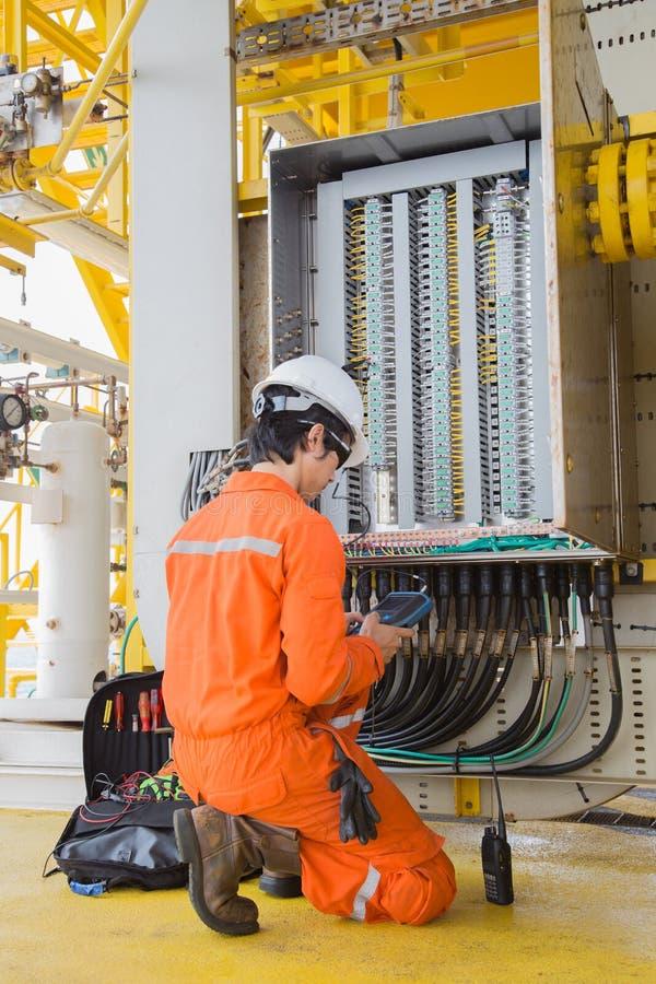 Het onderhouds elektrisch systeem van de elektro en instrumententechnicus bij zeeolie en gasverwerkingsplatform royalty-vrije stock foto's