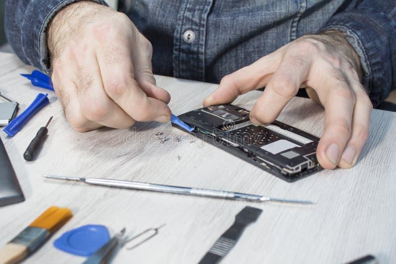 Het ondermijnen van de mobiele telefoondekking met een speciaal hulpmiddel Een de dienstwerknemer van mobiele telefoons herstelt  stock afbeelding