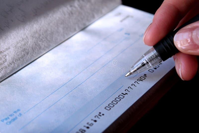 Het ondertekenen van een blanco cheque stock afbeeldingen