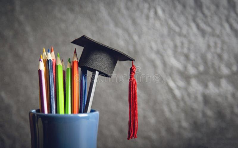 Het onderwijs en terug naar schoolconcept met graduatie GLB op potloden kleurt in een potloodgeval op donkere achtergrond stock afbeeldingen