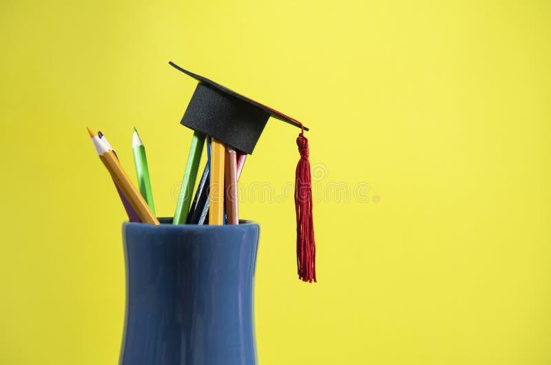Het onderwijs en terug naar schoolconcept met graduatie GLB op potloden kleurt in een potloodgeval op gele achtergrond royalty-vrije stock afbeeldingen