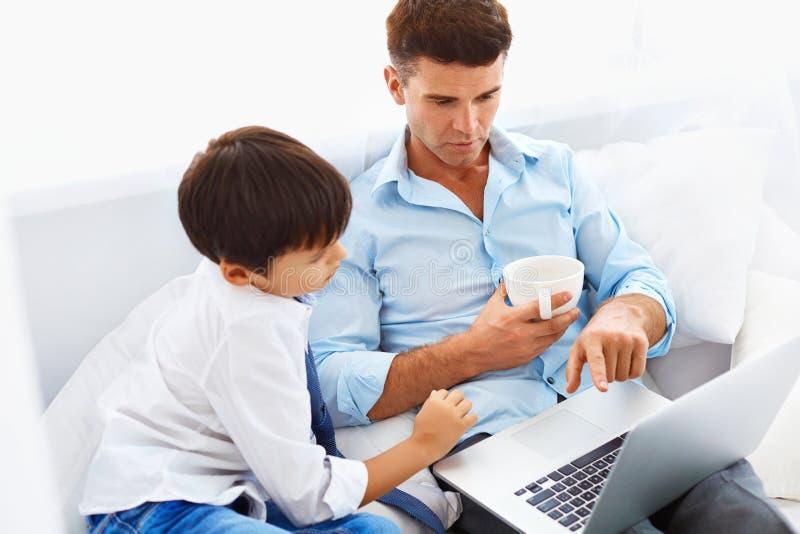 Het onderwijs van het huis Knappe vader die zijn zoon helpen om zijn thuiswerk te doen stock fotografie