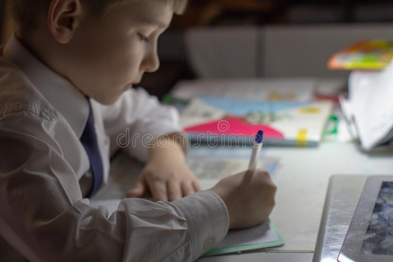 Het onderwijs van het huis Het huiswerk na school Jongen die met pen Engelse woorden met de hand op traditioneel wit blocnotedocu royalty-vrije stock afbeeldingen