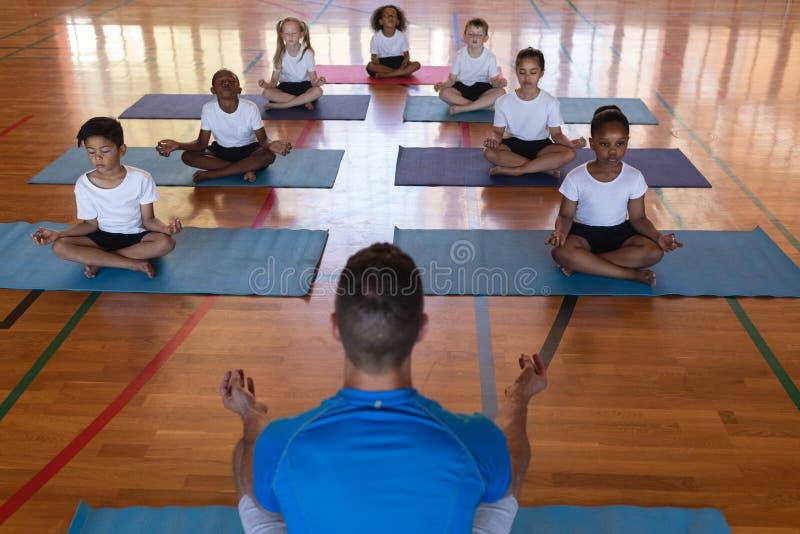 Het onderwijsyoga van de yogaleraar aan schooljonge geitjes in school royalty-vrije stock afbeelding