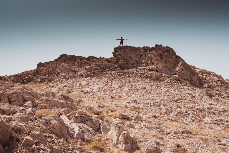 Het onderzoeken - het eenzame menselijke lopen in een rotsachtige woestijnvrijheid en van de van de avonturenlevensstijl en sport royalty-vrije stock fotografie
