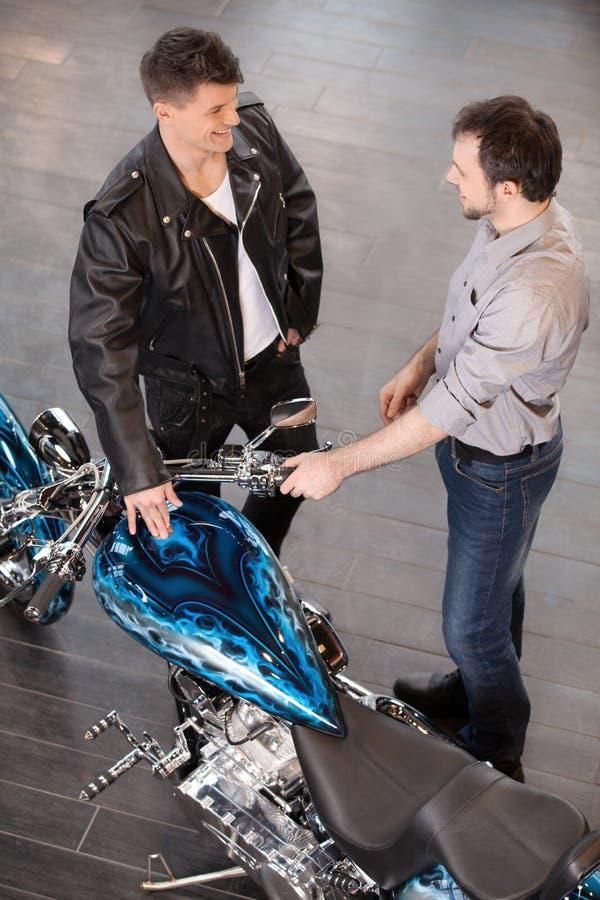 Het onderzoeken van motorfiets. Het vrolijke jonge verkoop uitvoerende raadplegen royalty-vrije stock afbeelding
