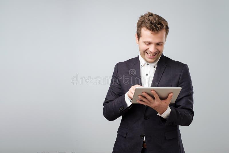 Het onderzoeken van nieuw gadget Zekere jonge knappe mens in blauw kostuum die aan digitale tablet werken stock fotografie