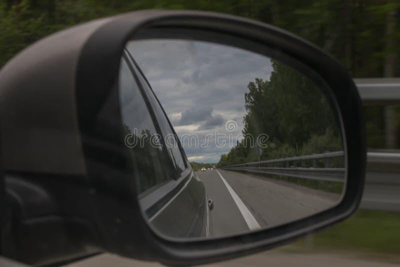 Het onduidelijke beeld van de motie Weergeven van de bosweg door de zijspiegel van de auto royalty-vrije stock fotografie