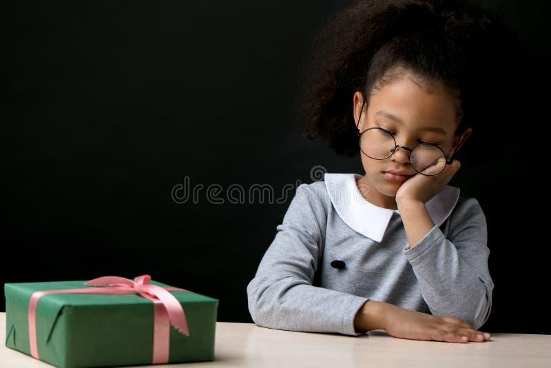 Het ongelukkige afromeisje leunt op haar kin en kijkt neer stock fotografie