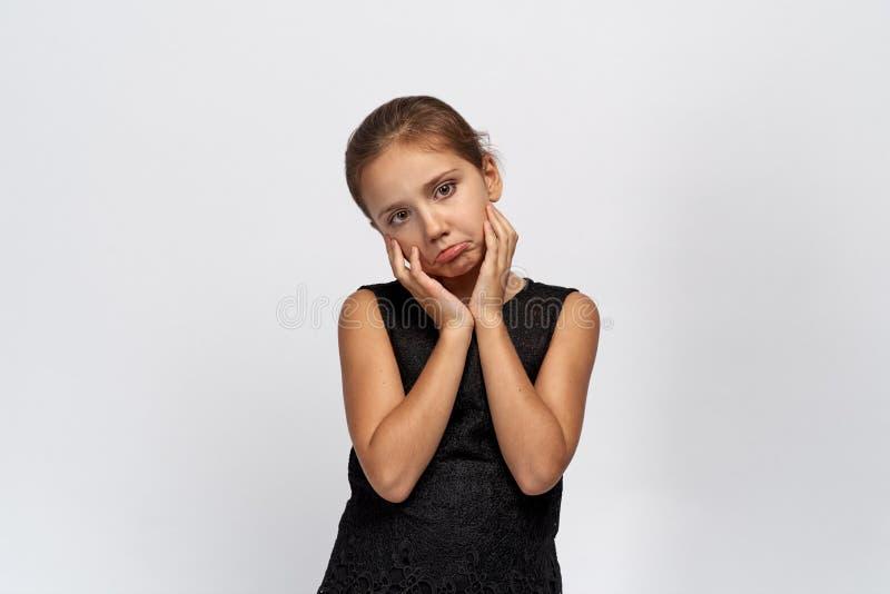 Het ongelukkige meisje onderzoekt de camera, plakt uit lip in wrok, die haar handen omhoog houden stock afbeelding