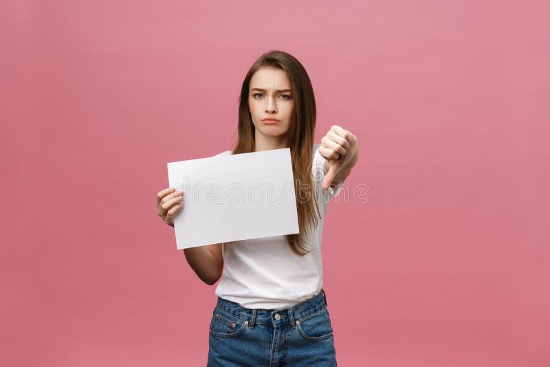 Het ongelukkige vrouw geven beduimelt onderaan gebaar met leeg document en negatieve uitdrukking en afkeuring stock afbeelding