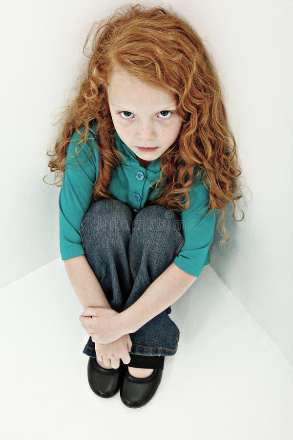 Het ongerust gemaakte Droevige Kind van het Meisje in het Zitten in Hoek stock afbeeldingen