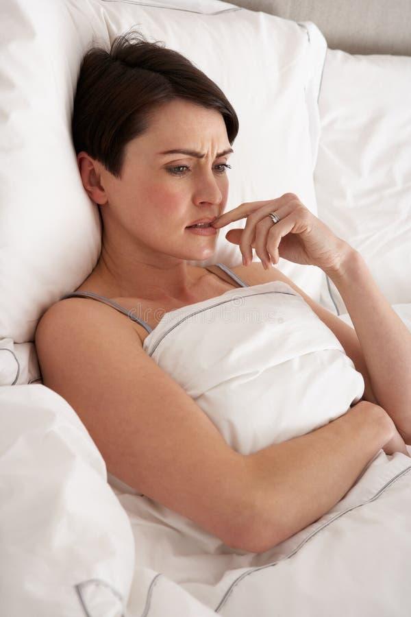 Het ongerust gemaakte Leggen van de Vrouw Wakker in Bed stock foto's