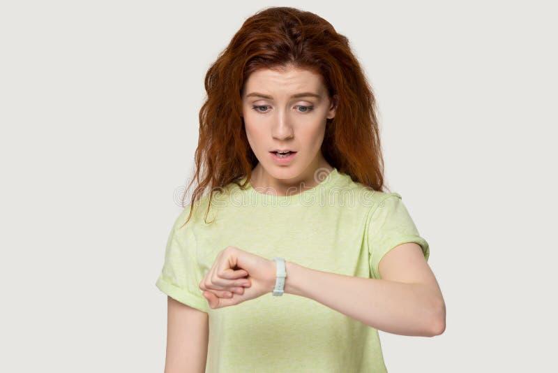 Het ongerust gemaakte roodharigemeisje bekijkt horloge controlerend tijd stock afbeelding