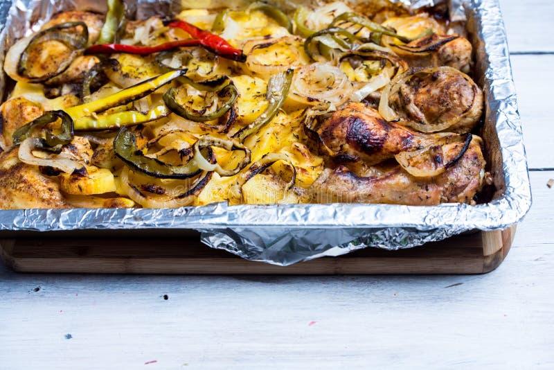 Het ongezonde maar traditionele eten - braadpan van aardappels, peper, uien en verse kip stock afbeeldingen