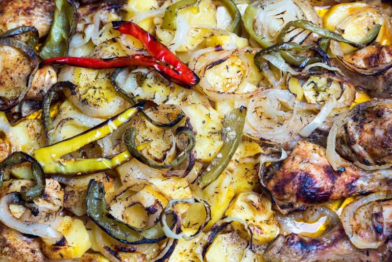 Het ongezonde maar traditionele eten - braadpan van aardappels, peper, uien en verse kip stock afbeelding