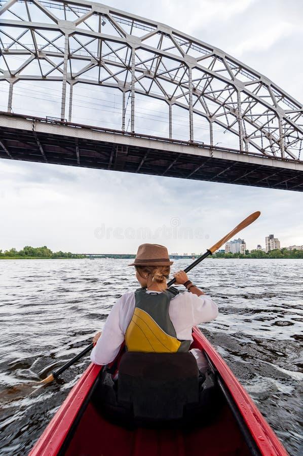 Het onherkenbare Jonge vrouw kayaking op een rivier Gelukkige meisjescanoeing onder de metaalbrug op een de zomerdag royalty-vrije stock afbeeldingen