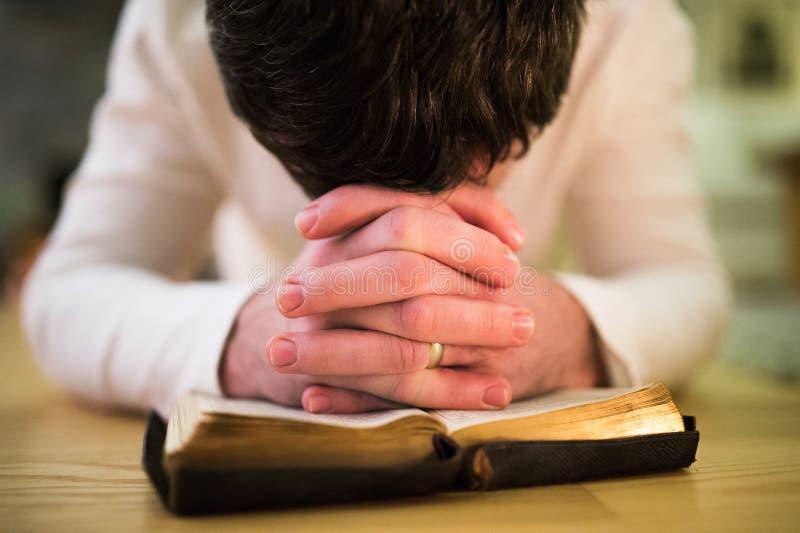 Het onherkenbare mens bidden, die op de vloer, handen op Bibl knielen royalty-vrije stock foto
