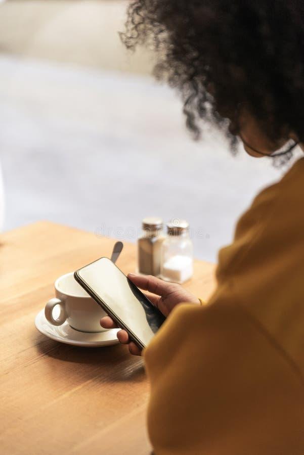 Het onherkenbare mooie afro Amerikaanse vrouw gebruiken mobiel in de koffiewinkel stock afbeelding