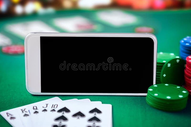 Het online casinoconcept, speelkaarten, dobbelt spaanders en smartphone royalty-vrije stock afbeeldingen