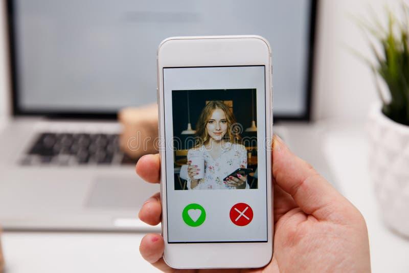 Het online dateren app in smartphone Mens die foto van mooi bekijken stock afbeeldingen