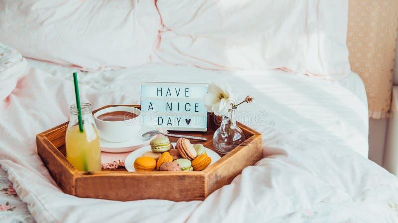 Het ontbijt in bed met heeft een aardige dagtekst op aangestoken vakje Koffiekop, sap, makarons, bloem in vaas op houten dienblad royalty-vrije stock foto