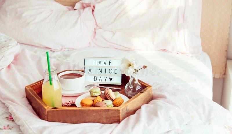 Het ontbijt in bed met heeft een aardige dagtekst op aangestoken vakje Koffiekop, sap, makarons, bloem in vaas op houten dienblad stock fotografie