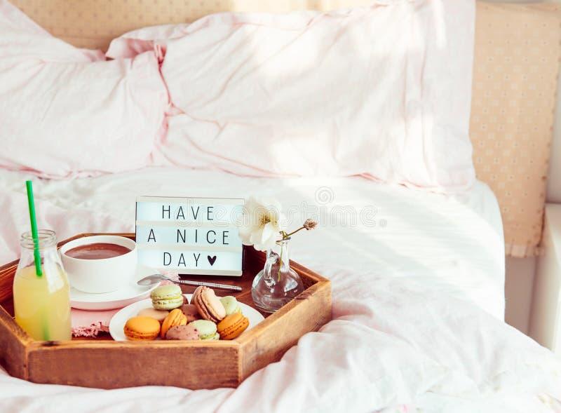 Het ontbijt in bed met heeft een aardige dagtekst op aangestoken vakje Kop van koffie, sap, makarons, bloem in vaas op houten die stock afbeelding