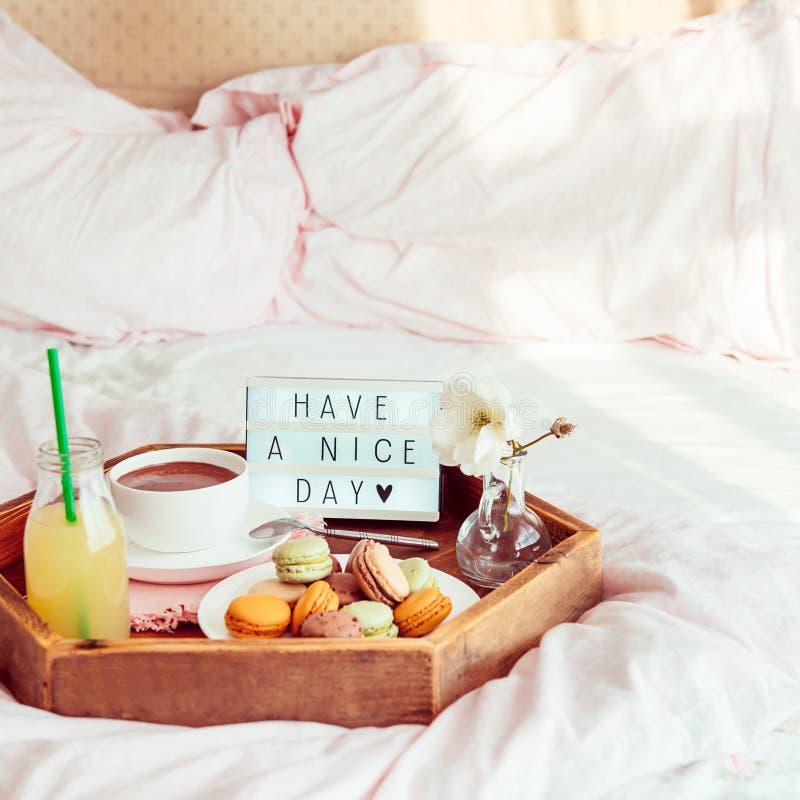 Het ontbijt in bed met heeft een aardige dagtekst op aangestoken vakje Kop van koffie, sap, makarons, bloem in vaas op houten die royalty-vrije stock afbeelding