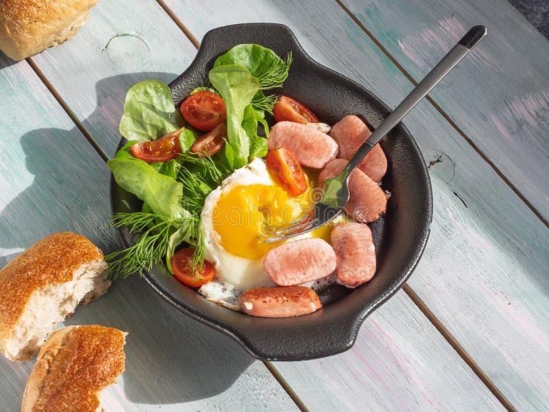 Het ontbijt begon te eten, bestaat het uit gebraden eieren en worsten in een zwarte pan met broodbroodjes op een houten dienblad stock foto